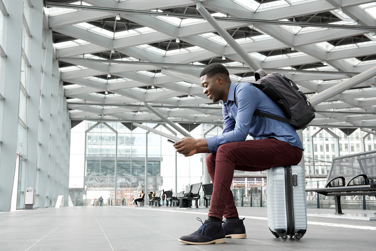 Man sitting at an airport looking at his mobile phone